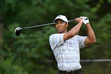 Tiger Woods, an African-American male in his early-30s, looks serious and wears a white hat and blue greyish polo shirt. On both his hands, he holds a golf club, after swinging it, and sports a white glove on his left hand.