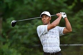 Un homme tient un club de golf dans ses mains derrière sa tête.