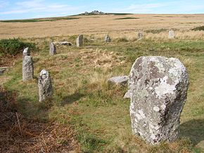 numerous standing stones arranged in an arc in a grassy field with a hill in the background