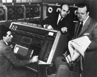 UNIVAC I - Remington Rand employees, Harold E. Sweeney (left) and J. Presper Eckert (center) demonstrate the U.S. Census Bureau's UNIVAC for CBS reporter Walter Cronkite (right).