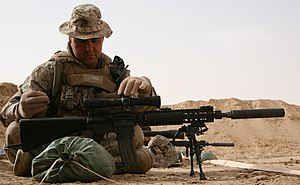 Designated marksman rifle -  A United States Marine adjusting the scope on a Mk 12 SPR