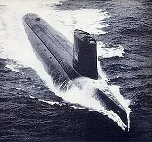 A submarine is running on the surface of the water at high speed, as evidenced by the long white wake around and behind the hull