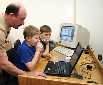 Personal computer - Children being taught how to use a notebook personal computer; an older (1990s-era) desktop personal computer's CRT monitor, keyboard, and mouse are visible in the background.