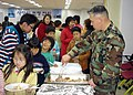 US Navy 061121-N-6609H-001 Master-at-Arms 1st Class Thomas Powell, a Sailor assigned to the Commander, Fleet Activities Chinhae (CFAC) Security Department, serves food to children at the Chinhae Volunteer Center.jpg
