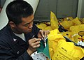 US Navy 090127-N-9134V-010 Boatswain's Mate 2nd Class Chinh Ho conducts preventive maintenance on a Stearns life preserver.jpg