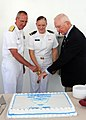 US Navy 100716-N-0569T-098 Ensign Anna Joy Hilton, center, Honor Graduate, cuts the cake at the end of the graduation ceremony for Surface Warfare Officer Introduction Course Class 10002.jpg