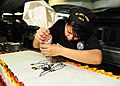 US Navy 111123-N-EZ913-060 Culinary Specialist Seaman Lindsey Ocampo, from Santa Ana, Calif., decorates a cake in preparation for Thanksgiving din.jpg