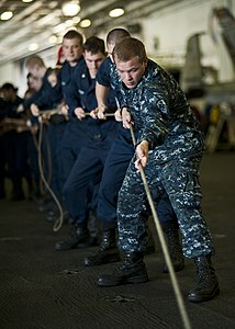 US Navy 111221-N-BT887-064 Cryptologic Technician (Collection) Seaman Kyle Kinderwater heaves a line for a sliding pad eye aboard the Nimitz-class.jpg