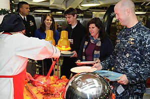 US Navy 111225-N-FU443-026 Sailors and family members wait in line during a Christmas dinner held aboard the aircraft carrier USS George H.W. Bush.jpg