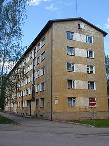 Foto av en relativt nedslitt bygning i fem etasjer