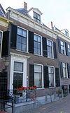 foto van Huis van parterre en verdieping met hoog schilddak, waarin dakvenster met vleugelstukken en fronton
