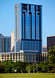 A view from Zilker Park of the building; the tower is topped out; the building is rectangular, and there are no setbacks; the building has a reflective blue facade; the tower appears to look like a tall rectangle stacked on top of another smaller rectangle.