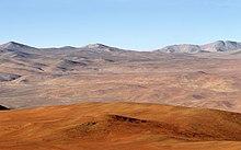Atacama Desert en malfono kun Andoj en distanco