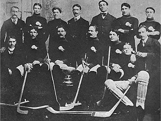 Dan Bain -  alt = Fourteen men pose around a silver trophy. Several are wearing identical sweaters with a buffalo logo over the left breast and are holding hockey sticks.
