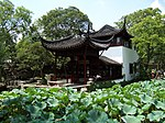 Chinese style pavilion near a pond with lotuses.