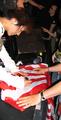 Yasuko-Onuki-signs-a-Rising-Sun-Flag-for-a-fan.png