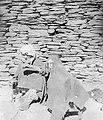 Пожилая женщина с веретеном у детской люльки в ауле Хуландой.jpg