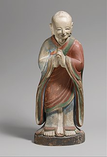 Monk in Chinese-style robes, bowing in respect with hands clasped and smiling