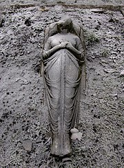 Headless stone statue of woman in draped cloth holding a sword