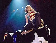 A blond woman riding a mechanical bull. She wears a T-shirt embedded with the flag of United States. Rays of light fall on her from above.