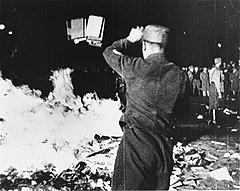 Photo noir et blanc prise de nuit, le 10 mai 1933, d'un autodafé public. Au centre et au premier plan, un homme en uniforme, de dos, lance des livres dans un feu, à sa gauche. À droite, en arrière-plan, un autre milicen surveille quelques badauds.