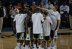 A team of basketball players are huddled together on a basketball court. The entire team is reaching to the center with one arm so that their hands touch.