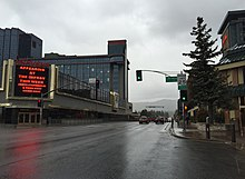 View of a rain-soaked roadway passing between tall hotel-casino buildings on either side and a traffic signal in the foreground, with signs indicating the Nevada state line at Lake Tahoe