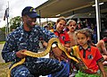 A Sailor holds a snake to show students from the Aboriginal and Islander Independent Community School during a community service event. (19966627132).jpg
