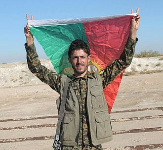 Sinjar Resistance Units - A Sinjar Resistance Units fighter carries the militia's flag