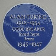 "A Blue plaque on a white wall with the words ""Alan Turing 1912–1954 CODE BREAKER lived here from 1945 – 1947"