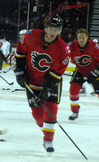 "A hockey player in a red uniform with black trim and a stylized black ""C"" logo on the chest skates toward the goal"