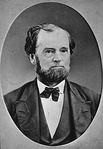 Oval, black and white shoulder-height portrait of a man in his forties or fifties, slightly balding wearing a suit