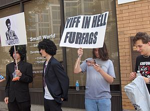 """Patriotic Nigras - Anti-furry protesters at Anthrocon 2007 wear afro wigs and Armani suits, and carry a sign saying """"Pool is Closed"""" in reference to Patriotic Nigras raids on Habbo Hotel."""