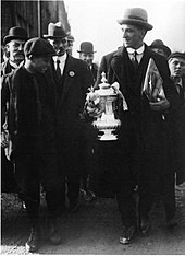 A tall man wearing a hat, shirt and tie and overcoat, holding a trophy. Next to and behind him are a crowd of people, looking in his direction.