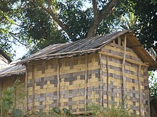 Small, rectangular one-room house with walls and roof made of flattened bamboo
