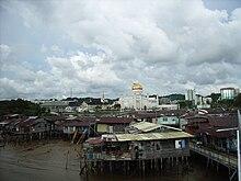 Photographie d'un quartier pauvre de la capitale, Bandar Seri Begawan. Au premier plan se trouvent des maisons sur pilotis délabrées. En arrière-plan se trouve la mosquée Omar Ali Saifuddin et des immeubles modernes en béton.
