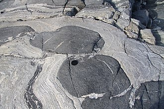 Competence (geology) - Boudinage of relatively competent metabasic sheet within quartzofelspathic gneiss