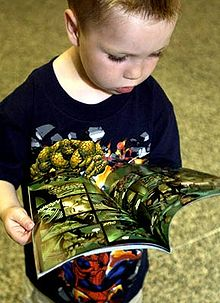 Un bambino che sfoglia un fumetto.