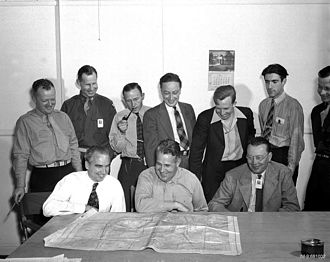 Norris Bradbury - Bradbury (left) sits at a table with Leslie Groves of the Armed Forces Special Weapons Project (center) and Eric Jette