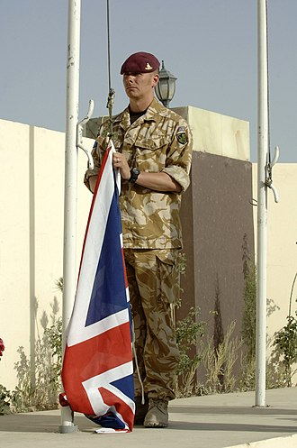 Operation Herrick - A British soldier of 21 (Gibraltar 1779–83) Air Assault Battery, Royal Artillery raising the Union Flag during a transfer of authority ceremony in Lashkar Gah, Helmand Province in May 2006.