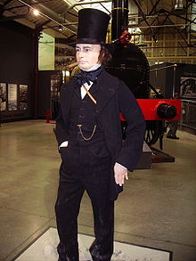 Inside a large building, a life size figure of a man in his late forties, dressed in nineteenth century jacket, trousers and waistcoat, with a prominent watch-chain across his chest. He wears a tall black stove-pipe hat, has long sideburns and has a cigar in his mouth. An old steam locomotive in the background.