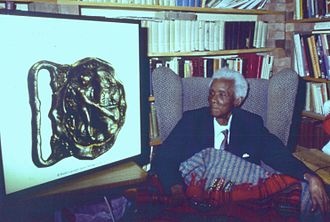 Barbados Cricket Buckle - C.L.R. James viewing an enlargement of the Barbados Cricket Buckle at his home in Brixton, London. 1988