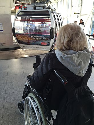 Emirates Air Line (cable car) - Woman boarding passenger gondola at Royal Victoria