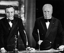 Photographie de Chaplin au visage bouffi et en costume de soirée avec Jack Lemmon à sa droite derrière un pupitre où se trouve une statuette et deux micros