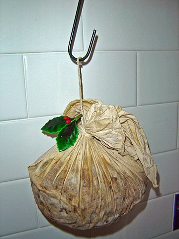 A giant lump of muslin-wrapped Christmas pudding hangs on a hook with a little branch of plastic holly attached