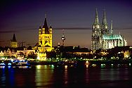 Cologne skyline at night with river Rhine in the foreground and famous Cologne Cathedral on the right. The towers of Town Hall (on the left) and Great St. Martin church (centre) are visible as well.