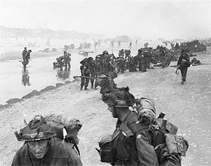 Tower Hamlets Engineers - Troops of 3rd Division on Queen Red beach, Sword area, circa 08.45 on 6 June 1944. In the foreground are sappers of 84 Field Company RE, part of No.5 Beach Group, identified by the white bands around their helmets.