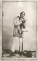 Photo of a man in blackface dressed in nondescript clothes behind a small table with a top hat at his feet.