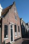foto van Huis met gepleisterde gevel met vlechtingen en toppilaster
