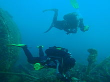 Two divers on a wreck. The one in the background is deploying an inflatable surface marker buoy as preparation for ascent